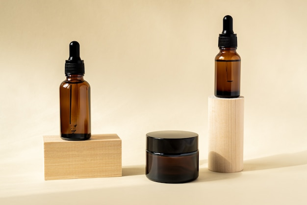 Natural essential oil, serum and cream in a brown glass bottle with a pipette on a wooden podium