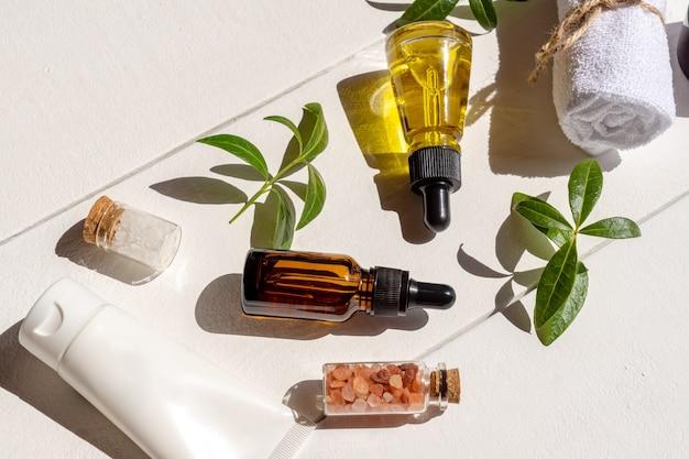 Натуральные эфирные масла в стеклянных флаконах-капельницах с гималайской солью, хлопковое полотенце на деревянном фоне. упаковка косметических средств других производителей.