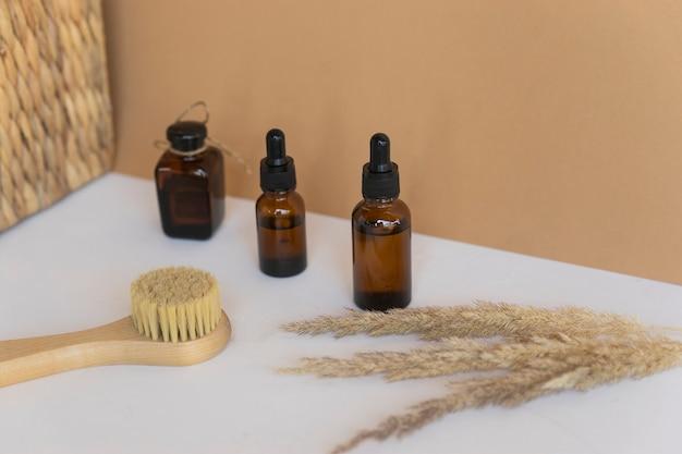 天然エッセンシャルオイル、スポイトボトルに入った美容液、フェイスマッサージ用のスパブラシ。天然の無印の化粧品