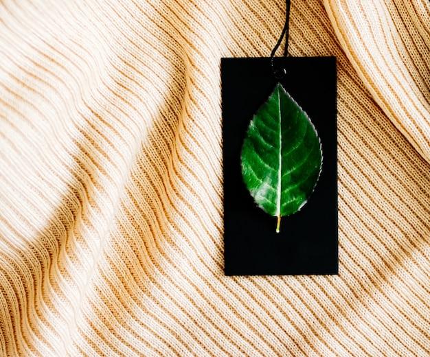 Натуральная ткань и зеленый лист на ценнике как экологичный плоский фон, экологичная мода и ...