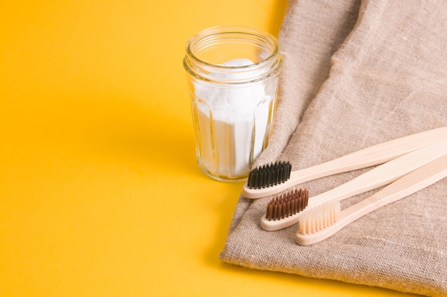 Natural fabric, several different bamboo brushes and a glass jar of soda on a yellow surface