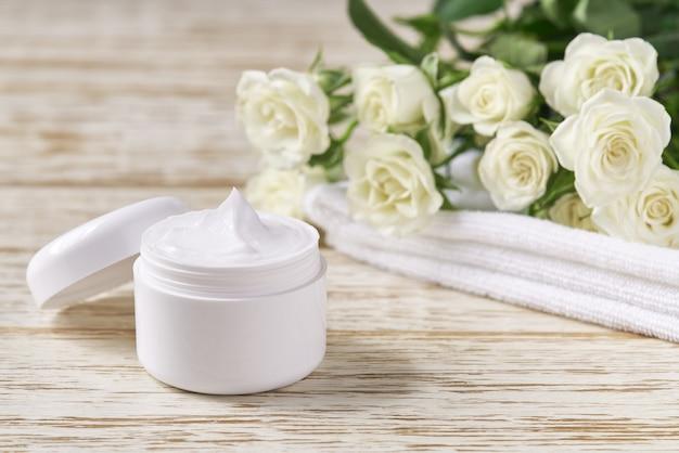 천연 페이스 크림이나 로션 민감성 피부, 하얀 장미 배경에 피부에 수분을 공급하는 유기농 화장품. 피부 정화 화장품 고급 크림 또는 비타민 스파 로션.