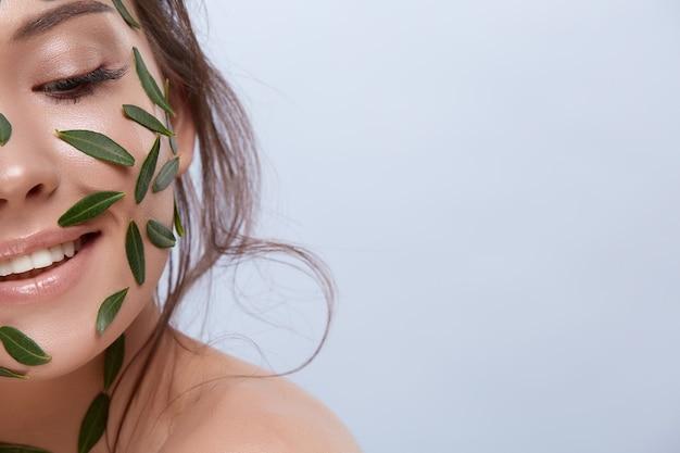 완벽한 피부와 녹색 잎이 회색 배경에 내려다 보이는 자연스러운 얼굴