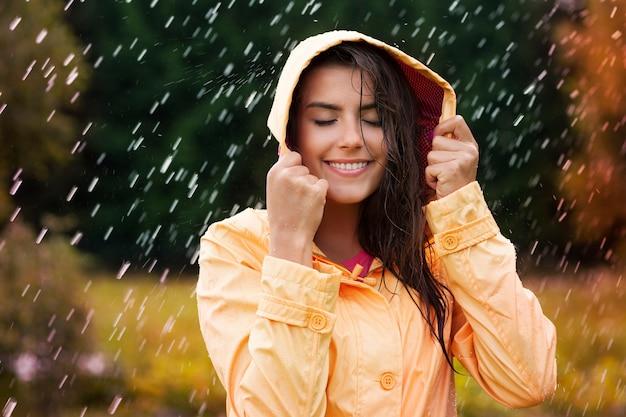 秋の雨の中の自然な女性の美しさ