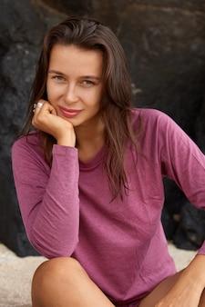 Modello femminile naturale con pelle sana, tiene la mano sotto il mento, vestito con abiti casual, si siede sulla spiaggia sabbiosa