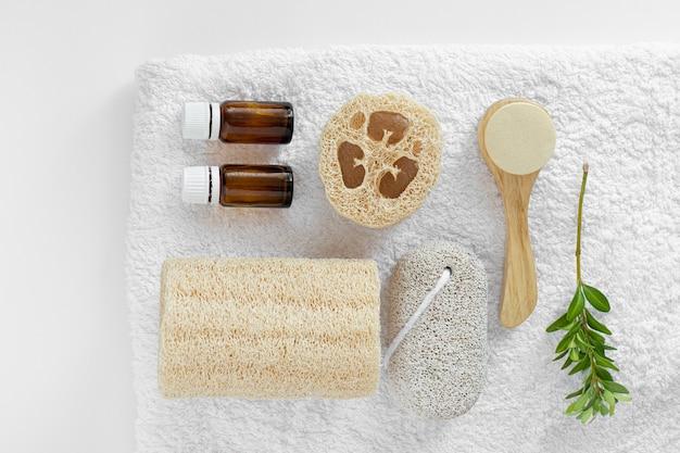 Натуральная флейта из предметов по уходу за кожей. люфа, стеклянные бутылки, пемза, люфа, средство для умывания, расческа на белом полотенце.