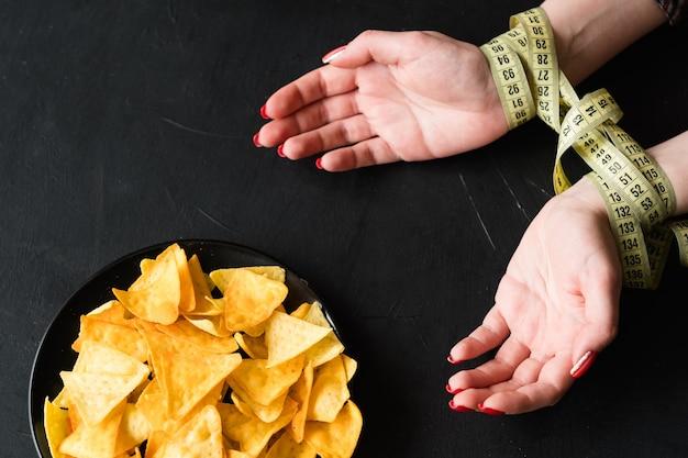 건강한 식생활을위한 천연 식품. 다이어트하는 동안 칩 스낵이 없습니다. 여자 손 측정 테이프와 함께 묶여있다.