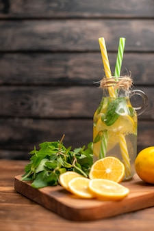 Natural fresh detox water served with tube mint and orange on a brown background