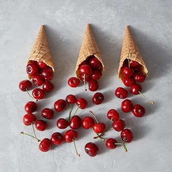 Натуральные свежие фрукты вишни в вафельных рожках для домашней выпечки на сером фоне с местом для текста. органическое вегетарианское сыроедение.