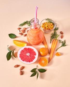紙の上のガラスの瓶に健康的なベジタリアンスムージーを準備するための天然の採れたての黄色い野菜や果物、ベリー、アーモンドナッツ。フラットレイ。