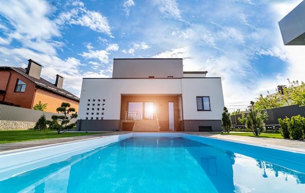 고급스러운 집에 물 수영장이 있는 자연 정원. 배경에 정원입니다. 깨끗한 물이 있는 수영장.