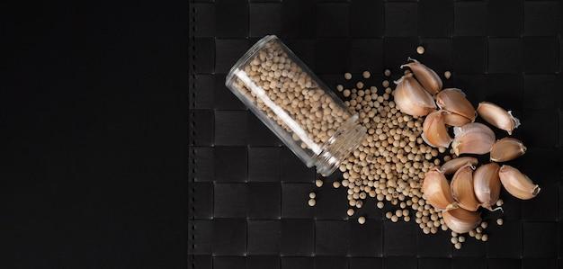 スタジオショットのプレートマット黒の背景にガラス瓶の天然ニンニクと白胡椒と白胡椒