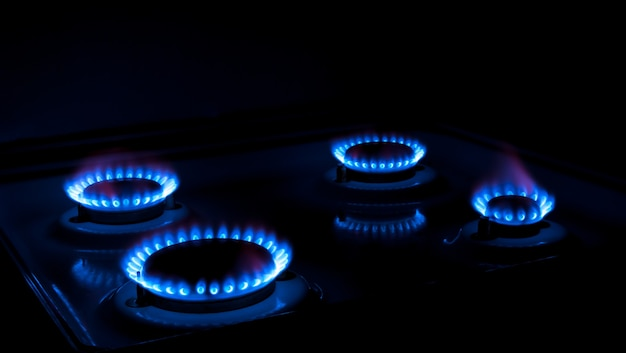 Natural gas burning a blue flames on black background