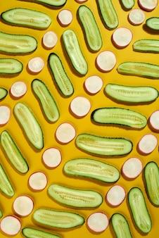 Естественный геометрический вегетарианский образец с кусочками свежесобранных овощей огурца и редиса на желтом фоне. диета здоровой концепции.
