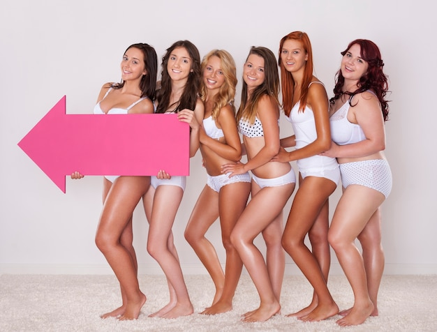Natural girls in underwear pointing by pink arrow
