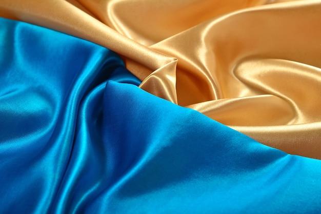 Натуральная золотисто-синяя атласная ткань в качестве фоновой текстуры