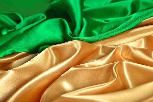 Натуральная золотисто-зеленая атласная ткань в качестве фоновой текстуры