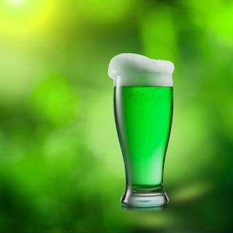 Натуральный зеленый алкогольный пивной напиток на зеленом размытом натуральном листе. счастливый день святого патрика концепция.