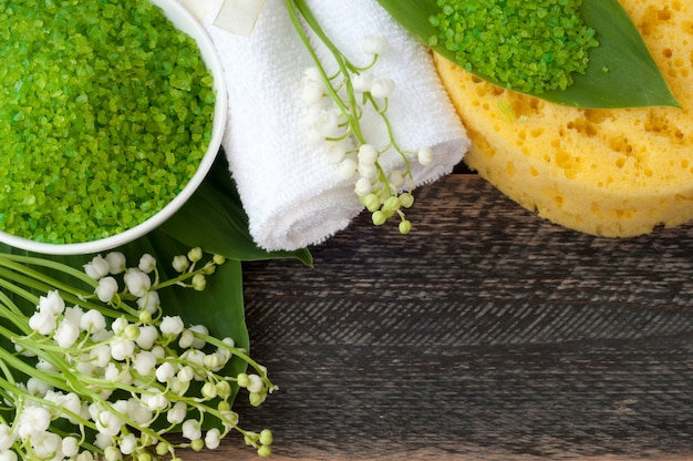 Natural green sea salt, towel, wisp of bast and hygiene items for bath and spa on old wooden board. selective focus