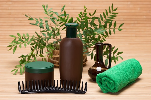 ナチュラルヘアケア化粧品。緑の植物の枝とシャンプー、ヘアマスク、くし、タオル