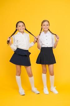 천연 헤어 익스텐션. 노란색 배경에 땋은 머리를 한 사랑스러운 어린 소녀들. 긴 머리 땋은 머리를 들고 귀여운 작은 아이들. 학교를 위해 머리를 땋고 스타일링합니다.