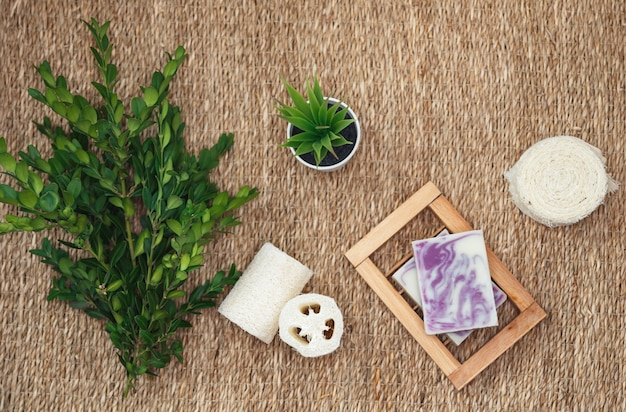 Natural handmade soap and accessories for body care. various spa related objects on straw background