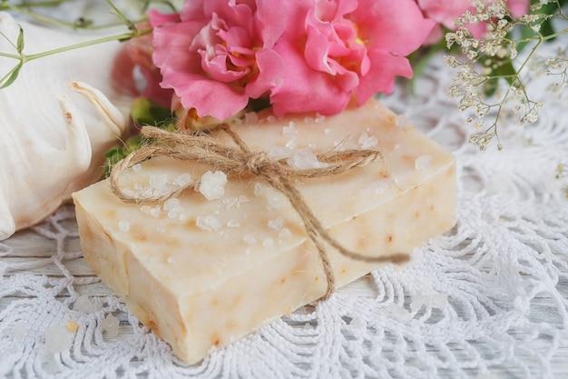 Натуральное мыло ручной работы и цветы на белом деревянном фоне. концепция спа.