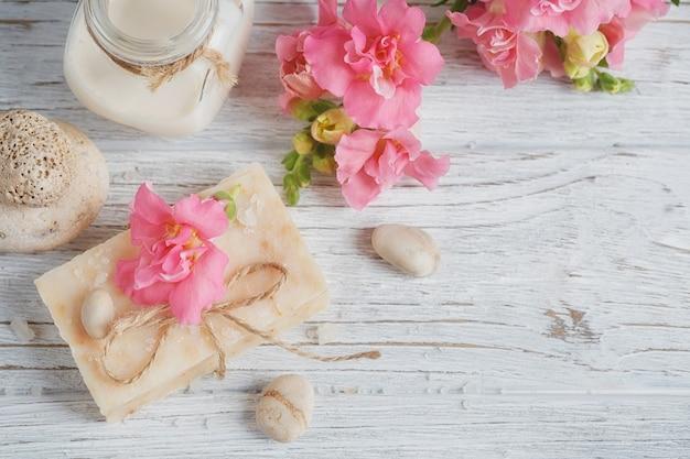 Натуральное мыло ручной работы, ароматическое масло и цветы на белом деревянном фоне. концепция спа. вид сверху