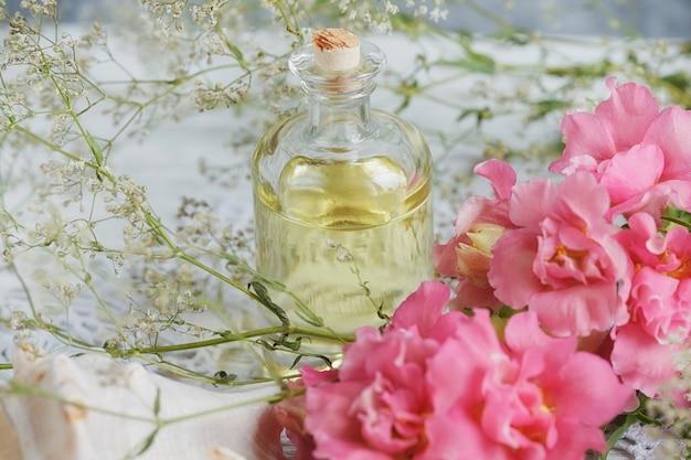 Натуральное мыло ручной работы, ароматическое масло и цветы на белом деревянном фоне. концепция спа.