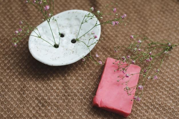 Натуральное мыло ручной работы с керамической мыльницей и цветами Premium Фотографии