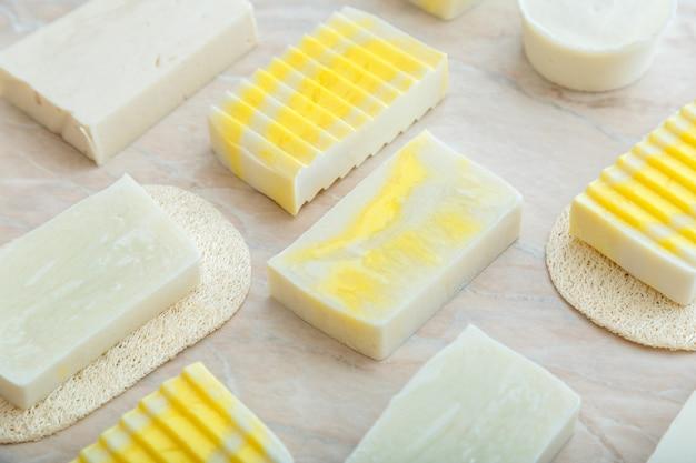 천연 수제 비누 바. 대리석 테이블에 스파 트리트먼트 패턴을 위한 수공예 향기로운 노란색 비누 바. 위생 스킨케어를 위한 세면도구 및 목욕 화장품.