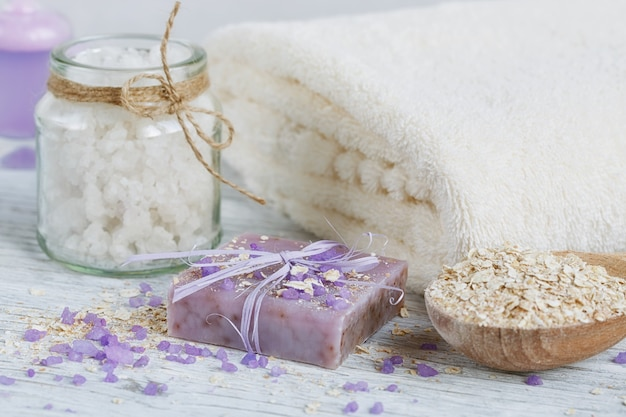 白い木の表面に天然の手作り石鹸、海塩、タオル、オート麦フレーク、小麦の穂。