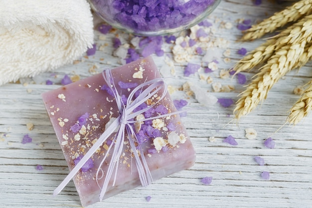 Natural handmade soap, sea salt, towel, oat flakes and wheat ears on a white wooden surface.