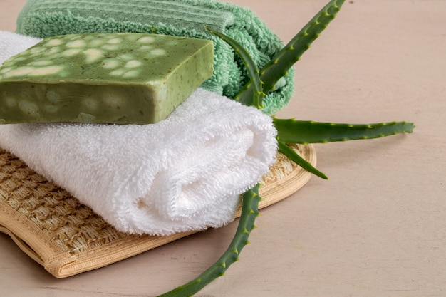Natural handmade soap, washcloth and towel on wooden .