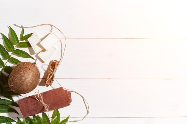 白い木製の背景にシナモン、茶色のタオル、ココナッツ、緑の葉と天然の手作り石鹸。上面図。スペースをコピーします。静物。フラットレイ。 spaセット。太陽フレア