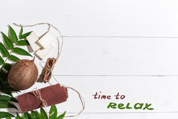 白い木製の背景にシナモン、茶色のタオル、ココナッツ、緑の葉と天然の手作り石鹸。上面図。スペースをコピーします。静物。フラットレイ。スパセット