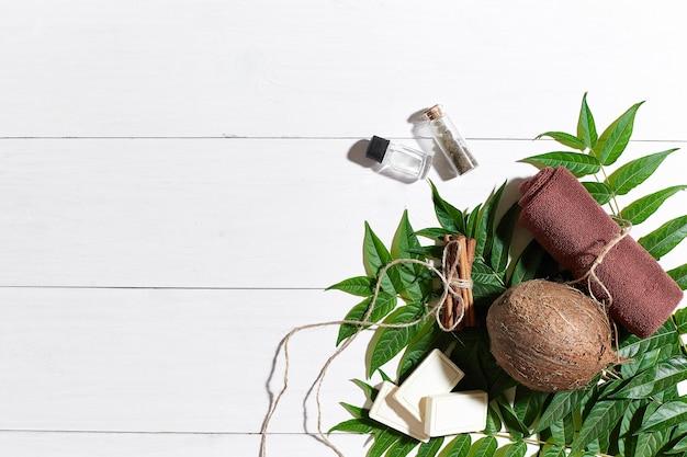白い木製の背景に油、茶色のタオル、ココナッツ、緑の葉と天然の手作り石鹸。上面図。スペースをコピーします。静物。フラットレイ。スパセット