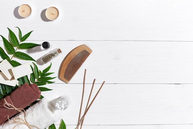 白い木製の背景にオイルキャンドル茶色のタオルと緑の葉と天然手作り石鹸