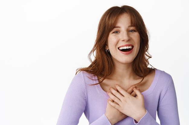 Natural happy girl, holding hands on heart, smiling white teeth, laughing sincere, looking at something funny and hillarious, standing in purple blouse on white