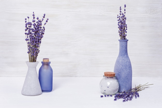 Natural healthcare concept. purple lavender and sea salt for body. bottles with lavender on wooden background.