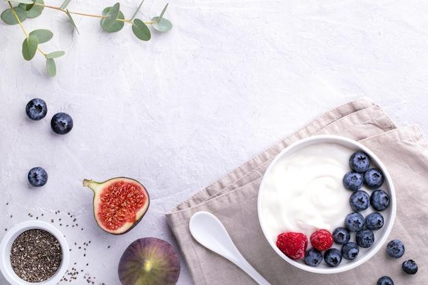 ブルーベリー、イチジク、チアシード、ラズベリーとライトグレーのテーブルに白いボウルに自然な健康的なスーパーフードの発酵ヨーグルト。画像はコピースペースと上面図です
