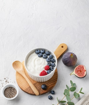 Natural healthy superfood fermented yogurt with blueberry, figs, chia seeds and raspberry in white  bowl on light gray table. image is copy space and top view