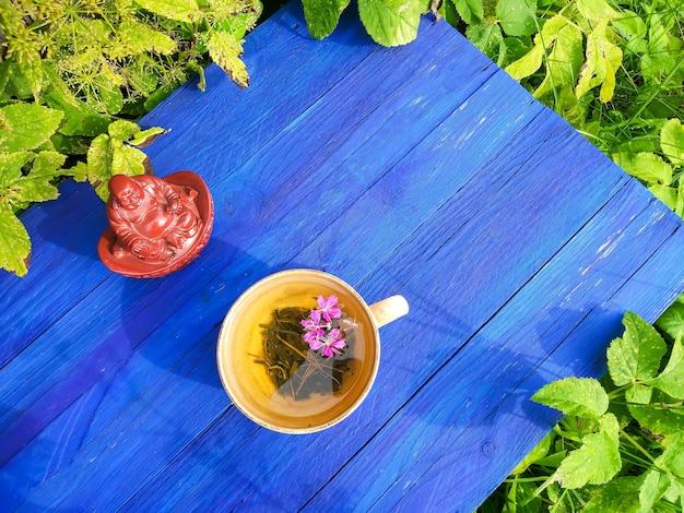 屋外の青い木の板に紫色の新鮮な花と医療用ファイアウィード植物nセラミックカップの葉を持つ天然ハーブティー。