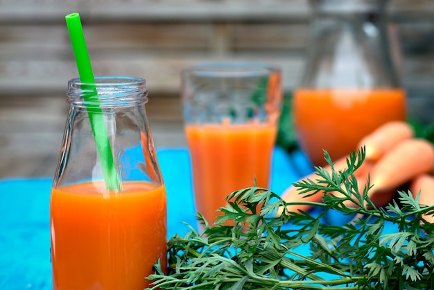 Natural homemade carrot juice in glass on an old wooden blue table in the background.