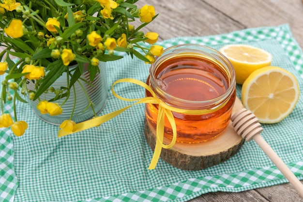Natural homemade honey in a glass jar with lemon on a wooden table.