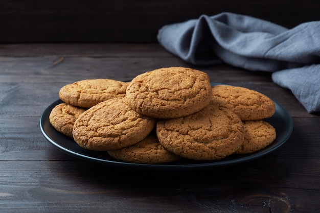 Natural homemade oatmeal cookies on a plate, dark wooden background, copy space.