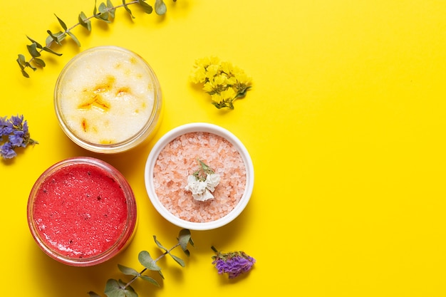 Натуральные домашние скрабы и гималайская соль на ярко-желтом фоне с копией пространства для текста. концепция домашнего спа.