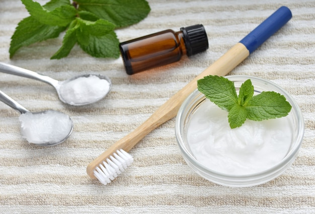 Natural homemade toothpaste, bamboo toothbrush and ingredients, baking soda, coconut oil, mint essential oil.
