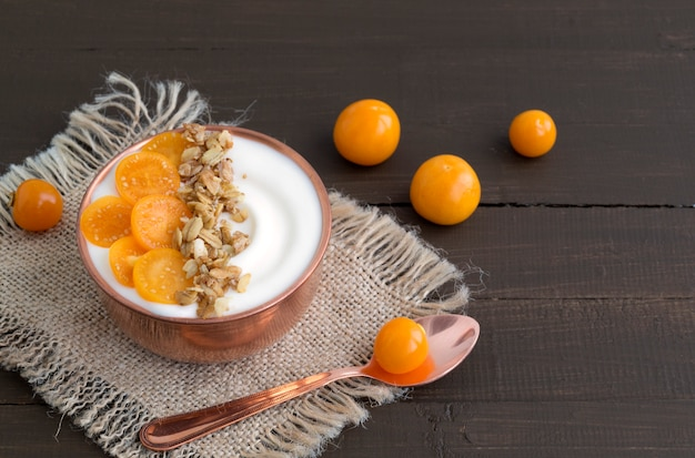 Natural homemade yogurt with ground-cherry on a wooden table.