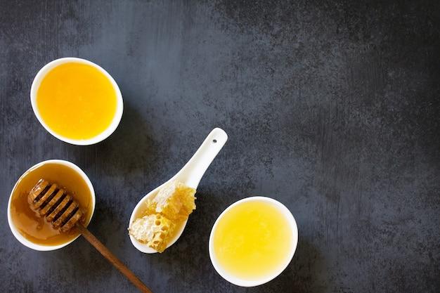 自然な蜂蜜の背景黒いスレートの背景にさまざまな蜂蜜と甘いハニカム